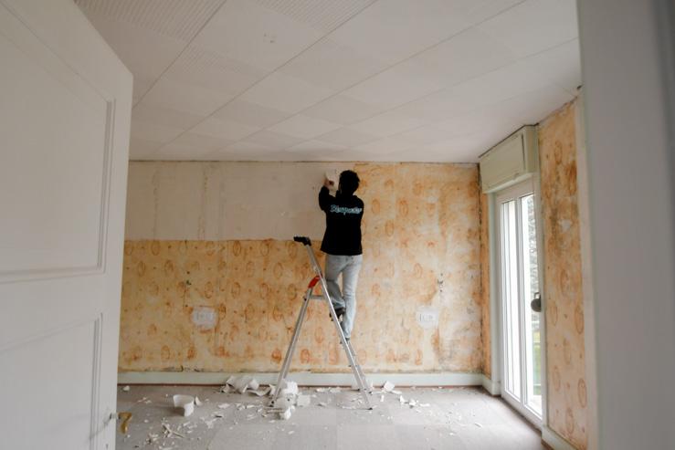 On enlève le papier peint sur les murs de la pièce